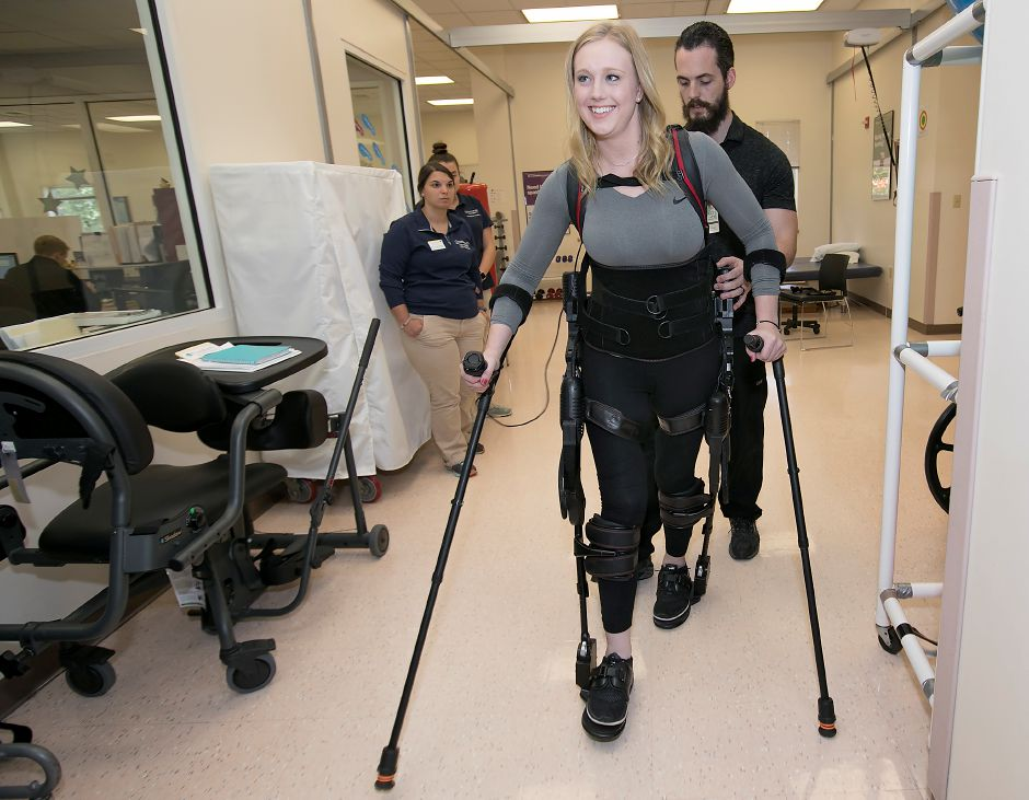 Physical therapist Tim Kilbride guides Jillian Harpin, 25, of Wolcott, who smiles while wearing an Ekso robot, a bionic device that enables her to walk, Friday, October 13, 2017. Harpin became paralyzed from the waist down after a fall from a balcony during Spring Break in Mexico last year. | Dave Zajac, Record-Journal