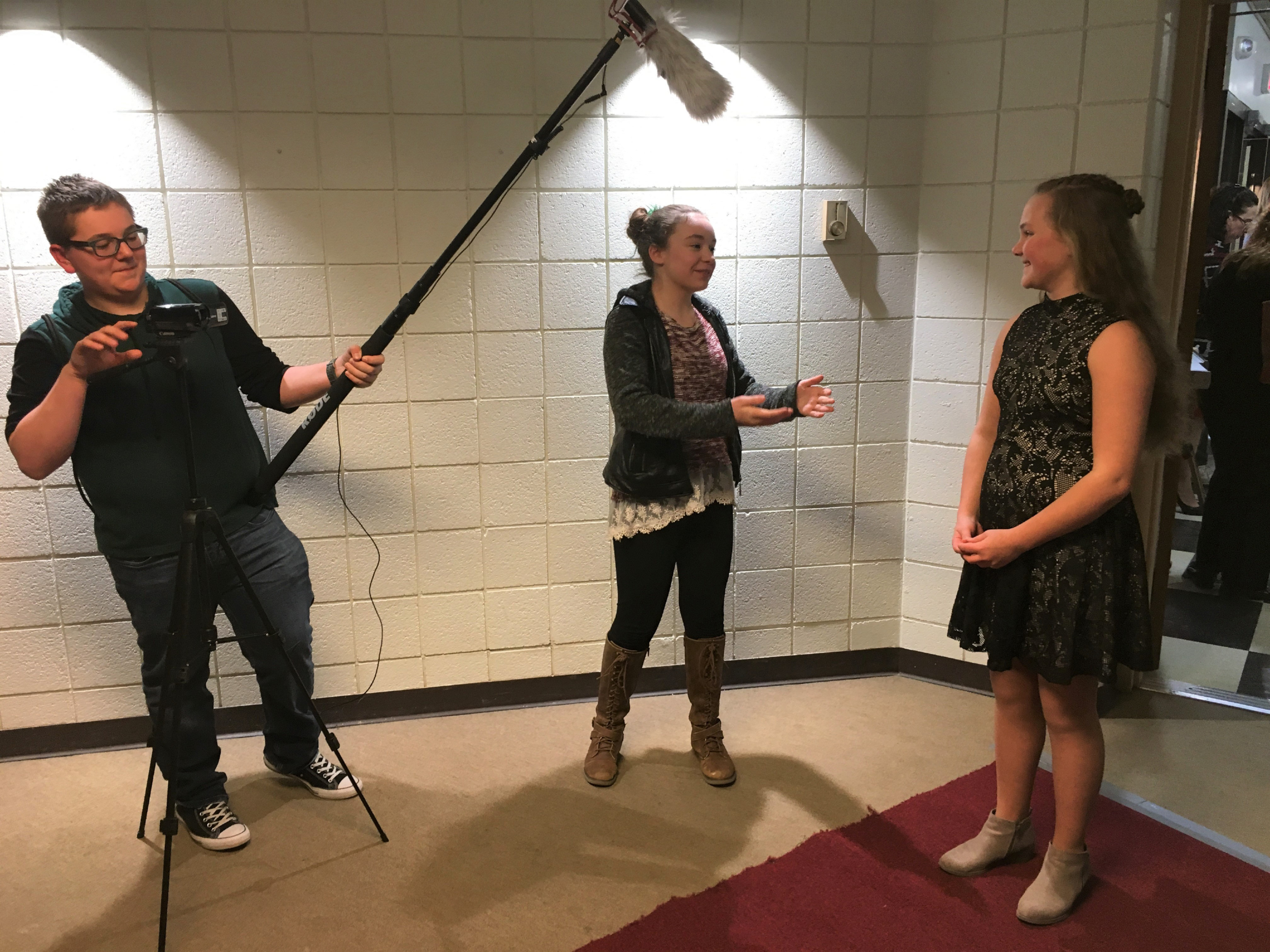 Dag Hammarskjold Middle School eighth-graders Corbin Hopkins, left, and Avery Loomis conduct a red-carpet interview with Moran Middle School sixth-grader Nele Koepfer at the premiere of the STEP class