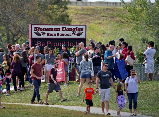 Parents and students arrive at Marjory Stoneman Douglas High School for an open house on Sunday, Feb. 25, 2018, in Parkland, Fla., as parents and students returned to the school for the first time since over a dozen were killed on Feb. 14. (David Santiago/Miami Herald via AP)