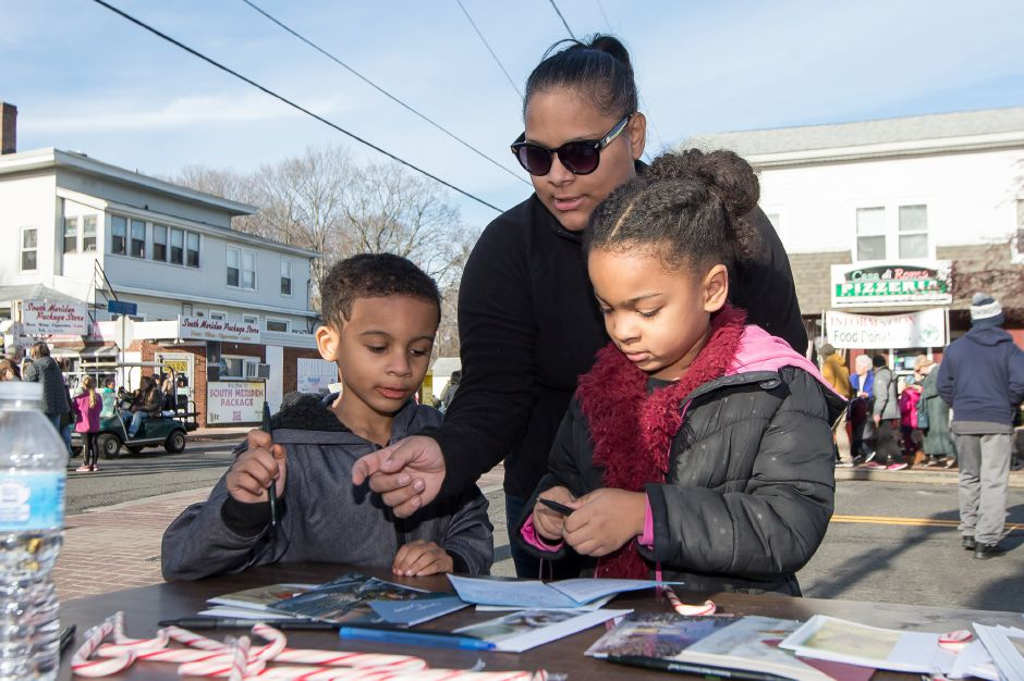 Chrissy Curz with daughter Eleina Largea 6 and son Amir Largea 5 write cards to service members and veterans at the American Legion Auxiliary booth Saturday during Christmas in the Village on Main Street in South Meriden December 1, 2018 | Justin Weekes / Special to the Record-Journal