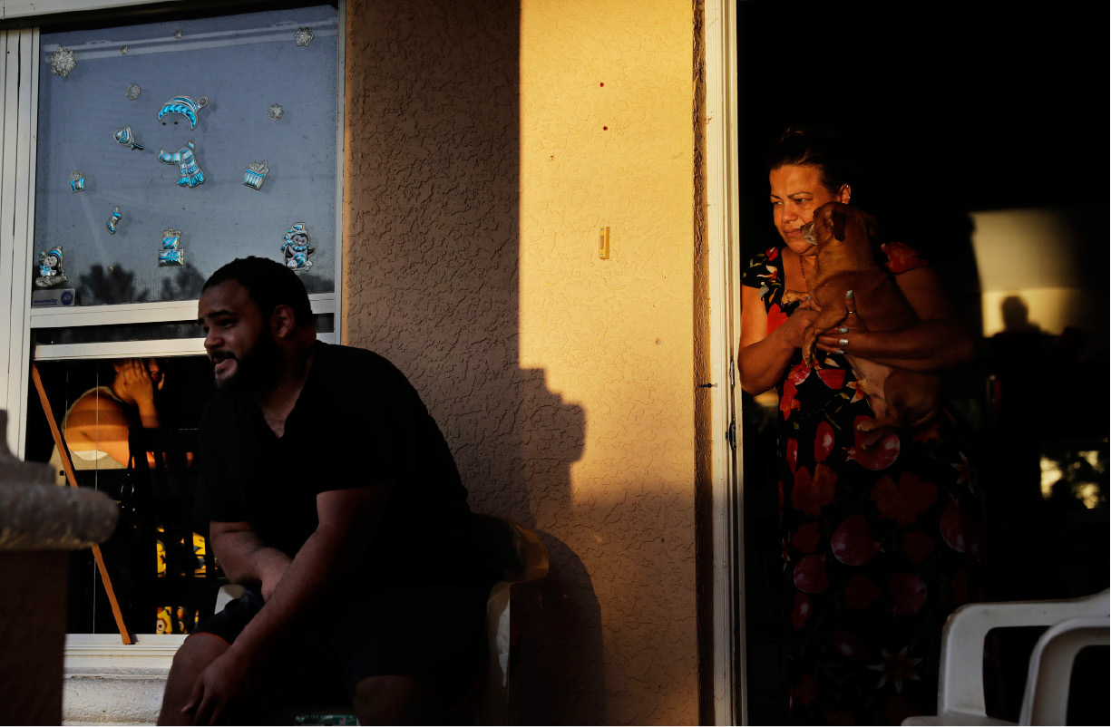 "Sandra Pagan, right, looks out from her front door while escaping the heat inside her home with her dog Goldo, nephew Misael Fernandez, center, and niece Lorraene Andaluz, in window at left, after Hurricane Irma flooded their neighborhood leaving them without power and impassable with their cars in Fort Myers, Fla., Tuesday, Sept. 12, 2017. ""It"