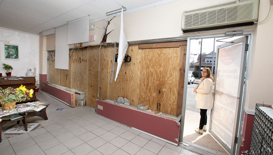 Jenny Rhee, owner of Sun Nails Salon, stands in the doorway of her boarded up business at 826 E. Center St., Wallingford, Thurs., Mar. 14, 2019. A vehicle crashed into the nail salon Thursday morning, significantly damaging the storefront. Dave Zajac, Record-Journal