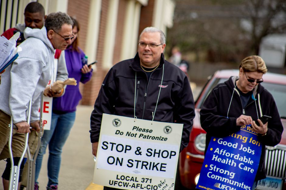 Richard Savarese, center, a Wallingford resident who has worked at Stop & Shop for 31 years, stands next to Cheryl Hobbs, of New Haven, who has also worked at Stop & Shop for 31 years, stand next to each other while on strike at the Meriden grocery store Thursday April 11, 2019. | Richie Rathsack, Record-Journal