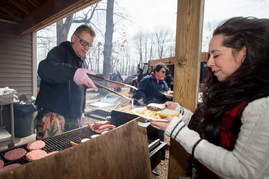 Stephanie Caron, of Wallingford, gets a cheeseburger from Paul Wieloch at the free lunch Saturday during the annual fundraiser at the Meriden Rod and Gun Club  for the St. Jude Children