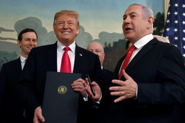 President Donald Trump smiles as he holds a proclamation as Israeli Prime Minister Benjamin Netanyahu, right, speaks in the Diplomatic Reception Room at the White House in Washington, Monday, March 25, 2019. Trump signed an official proclamation formally recognizing Israel