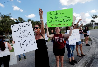 Angelina Lazo, 18, center, a senior at Marjory Stoneman Douglas High School, holds a sign with other students and parents at an intersection near the Marjory Stoneman Douglas High School in Parkland, Fla., Sunday, Feb. 18, 2018, where 17 people were killed in a mass shooting on Wednesday. Nikolas Cruz, a former student, was charged with 17 counts of premeditated murder. (AP Photo/Gerald Herbert)