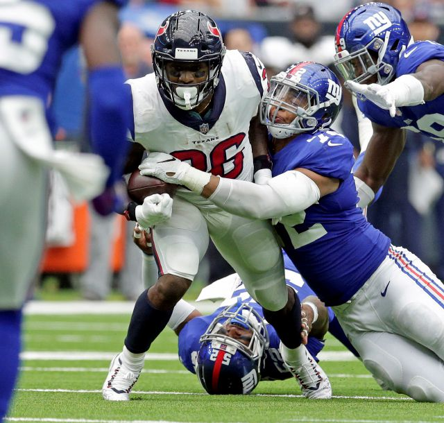 New York Giants defensive end Kerry Wynn (72) strips the ball away from Houston Texans running back Lamar Miller (26) during the second half of an NFL football game Sunday, Sept. 23, 2018, in Houston. The Giants recovered the fumble.(AP Photo/Michael Wyke)