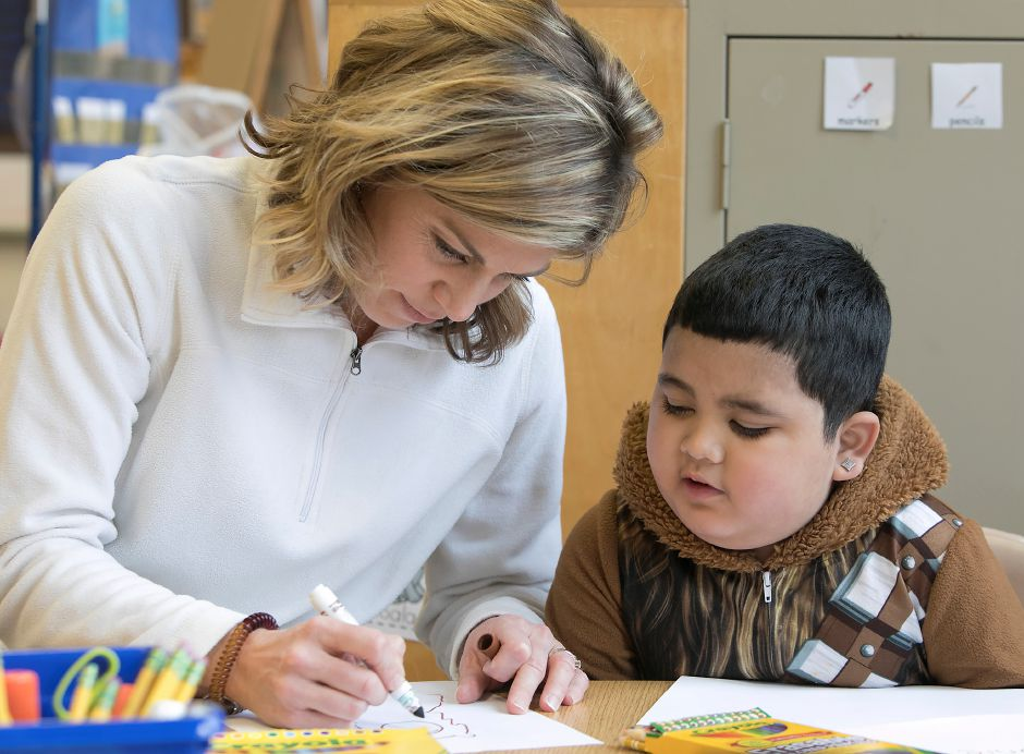 Kindergarten teacher, Kristen Bomengen, works with first-grade student Ethan Heng, 6, who wears Chewbacca pajamas while visiting her class during Pajama Day at Israel Putnam Elementary School in Meriden, Friday, Dec. 8, 2017. Dressed in pajamas, students and teachers took time from their lessons to make cards and activity books for children with cancer including Ethan, who has been diagnosed with brain cancer. Dave Zajac, Record-Journal