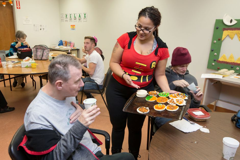 Corina DeJesus direct support professional offers Halloween cookies to David Pencek during a Halloween party at lunch Tuesday at the MidState Arc in Meriden October 31, 2017 | Justin Weekes / For the Record-Journal