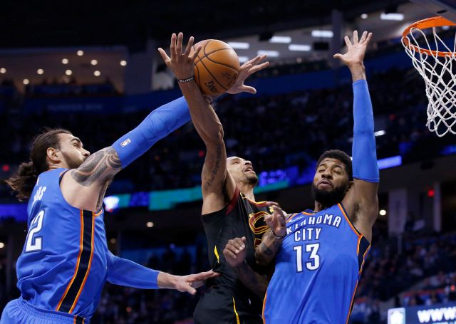 Oklahoma City Thunder center Steven Adams, left, knocks the ball away from Cleveland Cavaliers guard George Hill, center, as Hill shoots in front of forward Paul George (13) during the first half of an NBA basketball game in Oklahoma City, Tuesday, Feb. 13, 2018. (AP Photo/Sue Ogrocki)
