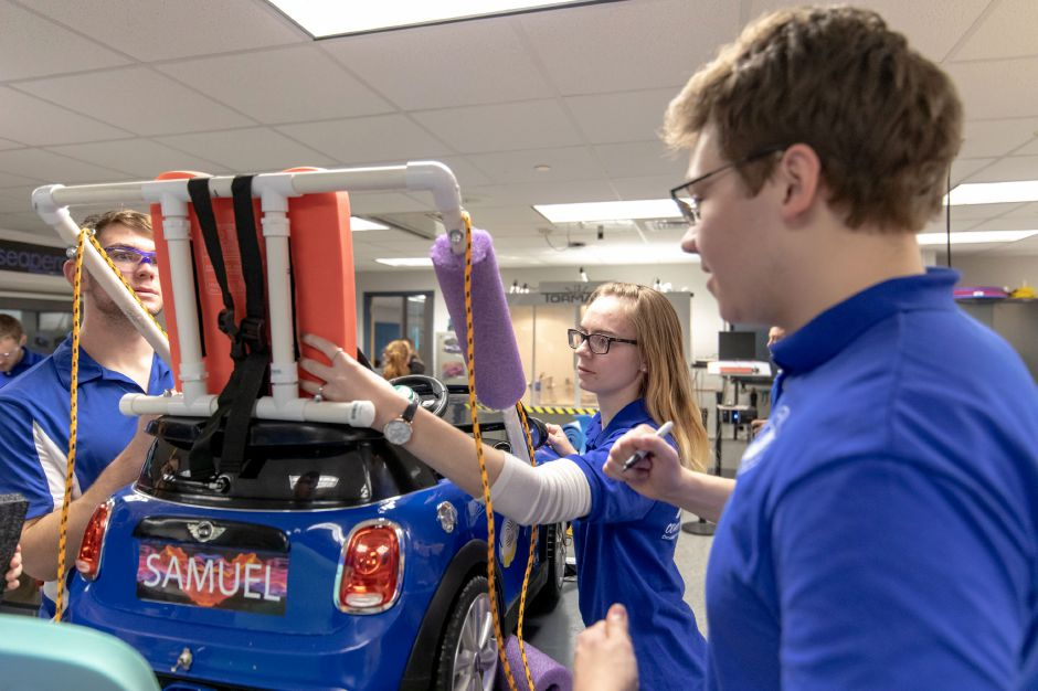 Stephanie Willoughby, a technology education student at Central Connecticut State University, adjusts part of the seat on a toy car. Working at Plainville High School, CCSU students helped local middle and high schoolers retrofit the cars for children with limited mobility on Dec. 7 and 8, 2018. | Devin Leith-Yessian/Plainville Citizen