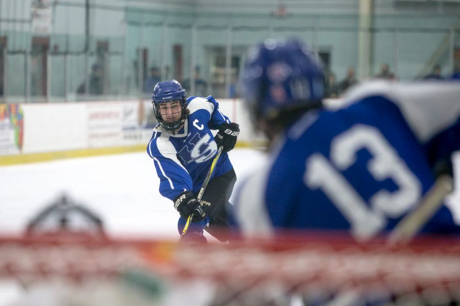 Southington's Chris Gambardella (6) puts a shot on goal as Nate Zmarlicki (13) positions himself for a redirect. Gambardella, a defenseman, is one of Hall-Southington's senior captains this season. | Justin Weekes / Special to the Record-Journal