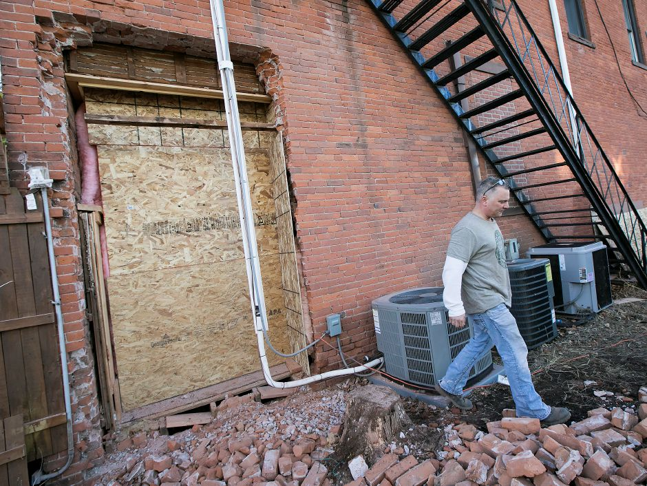 Tony Palmieri, of Palmieri General Contractors, walks next to damage done to the Hop Haus in Southington after the building was struck by a vehicle for the second time in less than six months, Monday, Feb. 12, 2018. Dave Zajac, Record-Journal