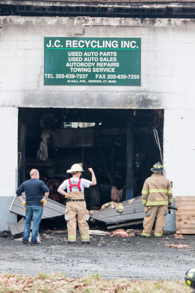 FIrefighters look at the damage left by a fire at 45 Hall Avenue in Meriden on Friday, April 13, 2018. The building, home to J.C. Recycling Inc., was deemed a total loss. | Devin Leith-Yessian/Record-Journal