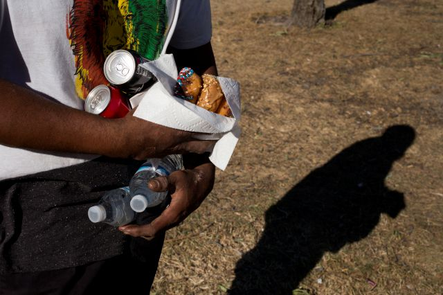 Homeless Jonathan Young, 40, carries donuts, soda and two bottles of water donated to him by church members in a homeless encampment set up on the Santa Ana River trail Saturday, Dec. 9, 2017, in Anaheim, Calif. Goodhearted neighbors heartbroken over the rising number of homeless in their communities are dishing out hot meals, providing mobile showers and handing out sandwiches to those in need. But some question whether they