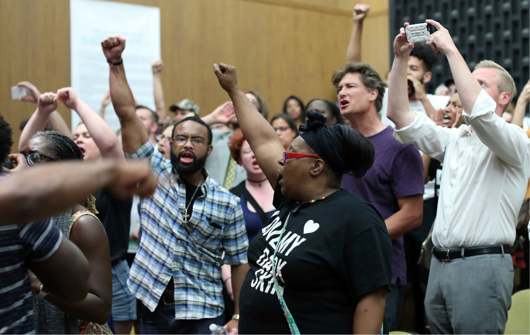 Protesters yell during the Charlottesville City Council meeting Monday, Aug. 21, 2017, in Charlottesville, Va. Anger boiled over at the first Charlottesville City Council meeting since a white nationalist rally in the city descended into violent chaos, with some residents screaming and cursing at councilors Monday night and calling for their resignations. (Andrew Shurtleff/The Daily Progress via AP)