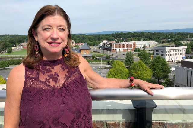 In this June 26, 2019 photo, Carolyn Sliger, rural programs coordinator at the Quillen College of Medicine at East Tennessee State University, poses at the rooftop bar at The Bristol Hotel in Bristol, Va. Ten medical students were on a tour of the city organized by a medical school with the aim of luring them to practice in rural communities facing health care shortages after graduation. (AP Photo/Sudhin Thanawala)