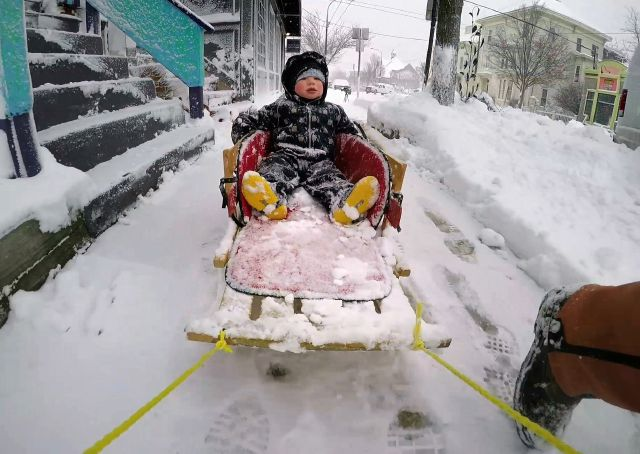 Gage Nathans, 2, gets a sled ride from his father John Nathans during a nor