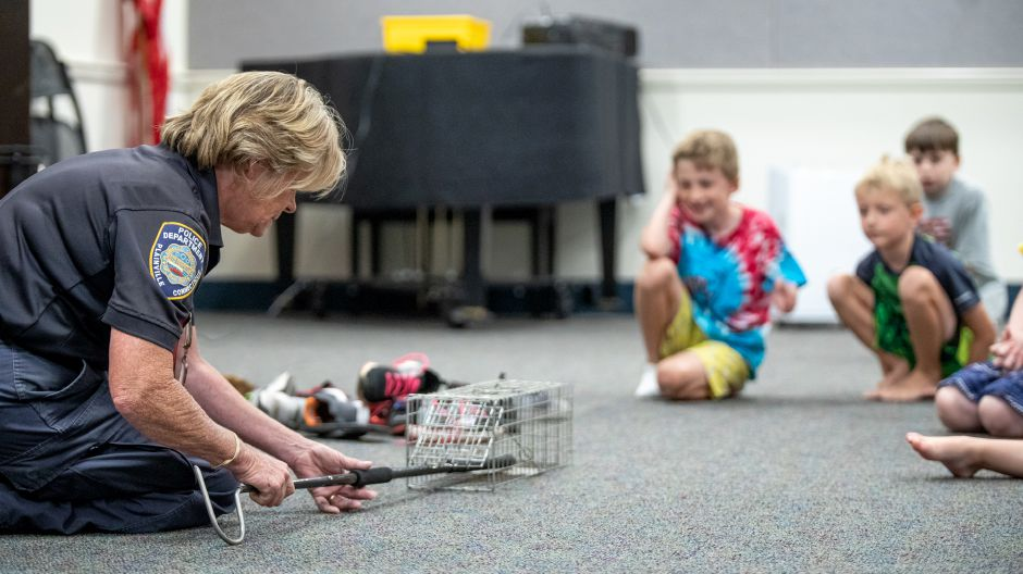 Plainville Animal Control Officer Donna Weinhofer shows a crowd of children one of the traps she uses for small animals. Weinhofer visited the Plainville Public Library Tuesday night to help families understand the animals which live around them. | Devin Leith-Yessian / Plainville Citizen