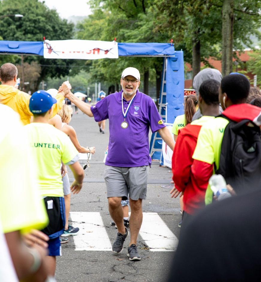 William Petit is cheered by the crowd after crossing the finish line at the Chip's Family Restaurant 5k Road Race. The Petit Family Foundation holds the race every year to raise money for the foundation