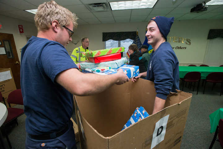 Meriden Fire fighters Ben Bischoff left and Justin Craig help to pack gifts for the Spirit of Giving Saturday at Hunters Ambulance in Meriden. The annual event gives to families in need with special delivery from volunteers, The Meriden Police and Fire Departments and Hunters Ambulance  Dec. 17, 2016 | Justin Weekes / For the Record-Journal