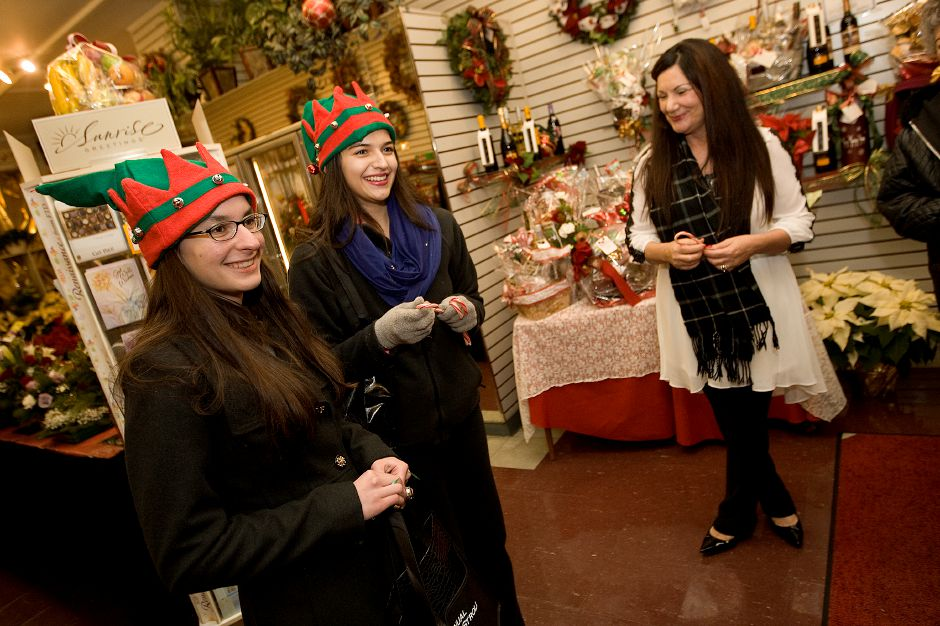 Lyman Hall students, Anna Aldrich, 16, left, and Alexa Malchiodi, 15, offer candy canes to patrons and staff of Wallingford Flower Shoppe, including Donna Greco, right, during the 5th annual Wallingford Holiday Stroll, Friday, December 6, 2013. | Dave Zajac / Record-Journal