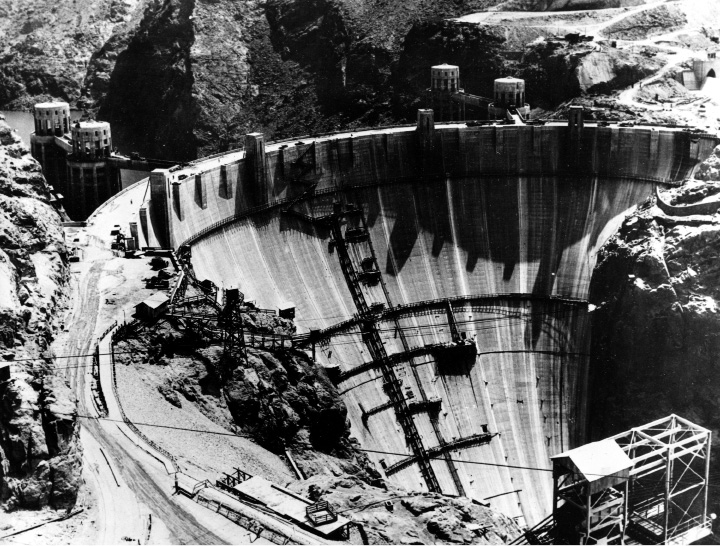 This aerial view shows a crest of the Hoover Dam, aka Boulder Dam, showing the highway leading across it on July 16, 1935.  The road, soon to be opened to the public, will provide an easy route between Las Vegas, Nev., and Kingman, Arizona.  The intake towers jut up on the other side of the dam in Boulder City, Nevada.  (AP Photo)