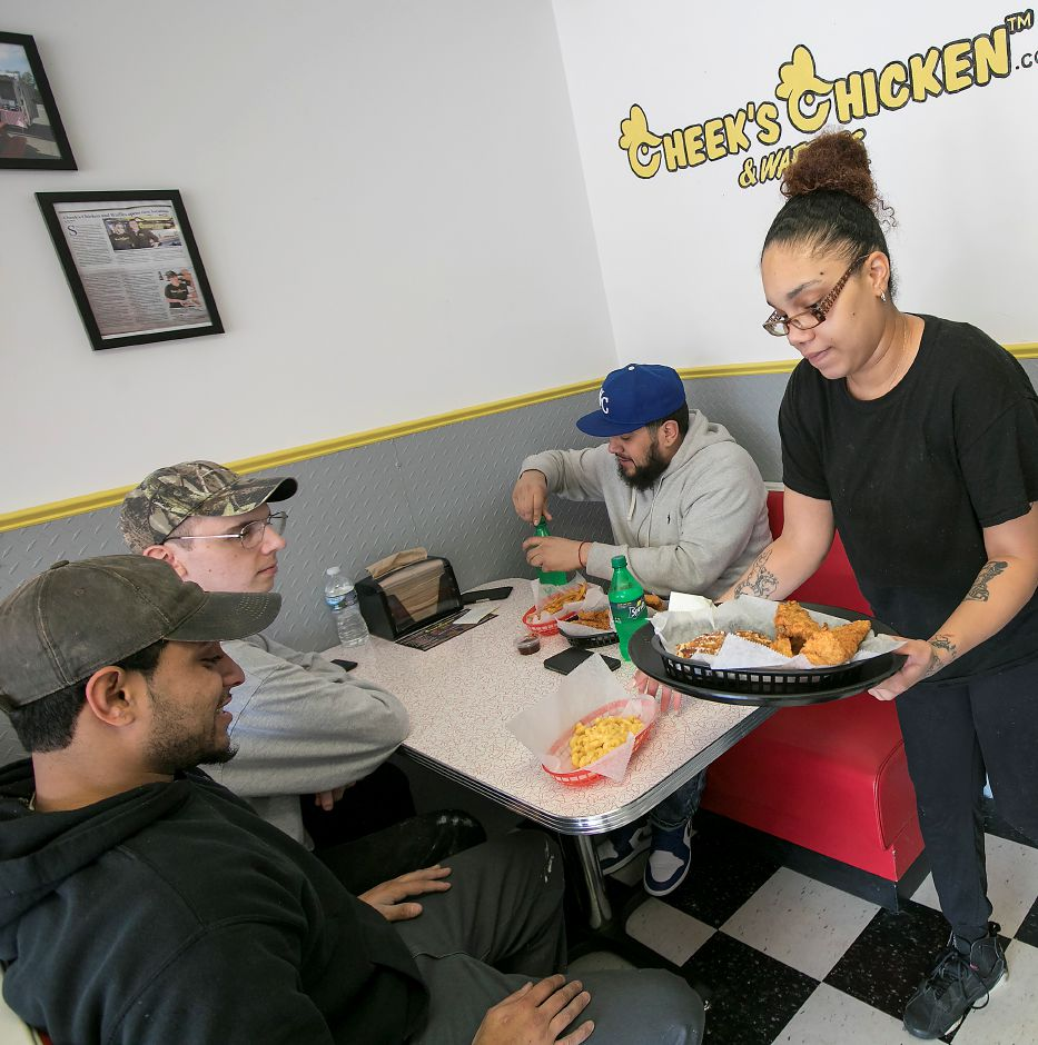 Above: Server Tiffany Parris, of Meriden, brings an order Wednesday to, left to right, Manuel Mateo, of Meriden, Jake Sizemore, of Wallingford, and Walter Martinez, of Meriden, during lunch at the new Cheek
