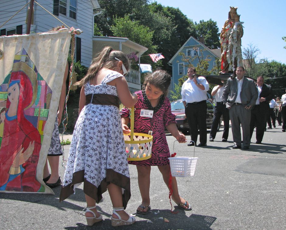 Gabriella Luca, 7, shares flower petals with Celina Carabetta, 5, to drop in front of a procession honoring Our Lady of Mount Carmel on Sunday. Domenico Parillo, left, Simone Parillo, middle, and Joseph DiBacco, left, carry a statue of the Virgin Mary down the streets around the Church, July 12, 2009. | Richie Rathsack, Record-Journal