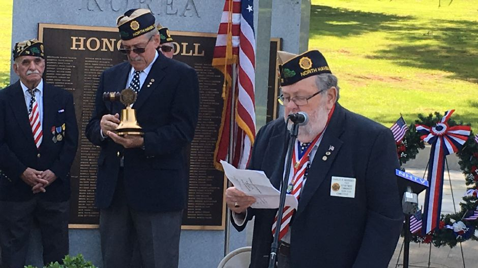 American Legion Post 76 Commander Charles Morrissey reads the names of Legionnaires who died in the past year during the Memorial Day service on the North Haven Town Green on Saturday, May 26, 2018. | Lauren Takores, Record-Journal