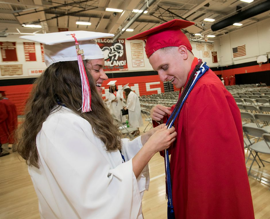 Graduate Rachel Kaplan assists fellow graduate Christian Horgan, 18, before the start of graduation ceremonies at Cheshire High School, Thursday, June 21, 2018. Dave Zajac, Record-Journal