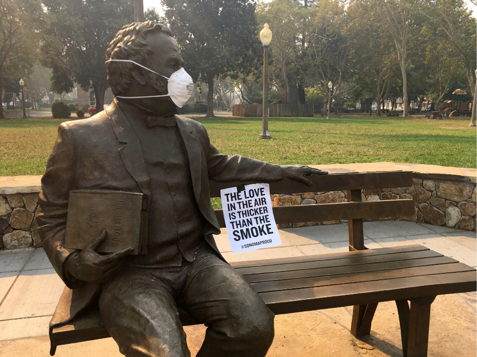 A note and face mask are seen on a statue in a downtown park filled with smoke from a wildfire in Sonoma, Calif., on Thursday, Oct. 12, 2017. Search-and-rescue teams, some with cadaver dogs, started looking for bodies Thursday in parts of California wine country devastated by wildfires, authorities said, sounding a warning that more dead were almost sure to emerge from the charred ruins.(AP Photo/John Mone)