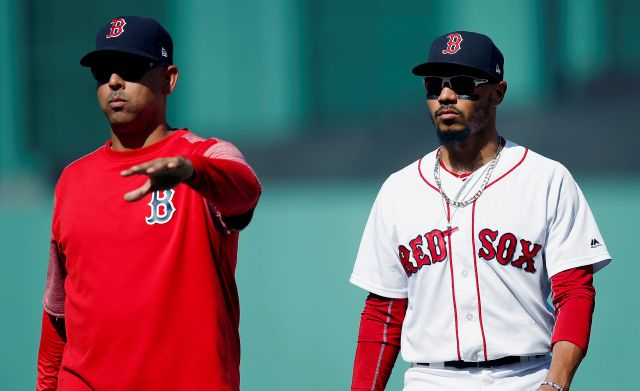 FILE - In this Sept. 16, 2018, file photo, Boston Red Sox manager Alex Cora, left, escorts Mookie Betts off the field during the sixth inning of the team