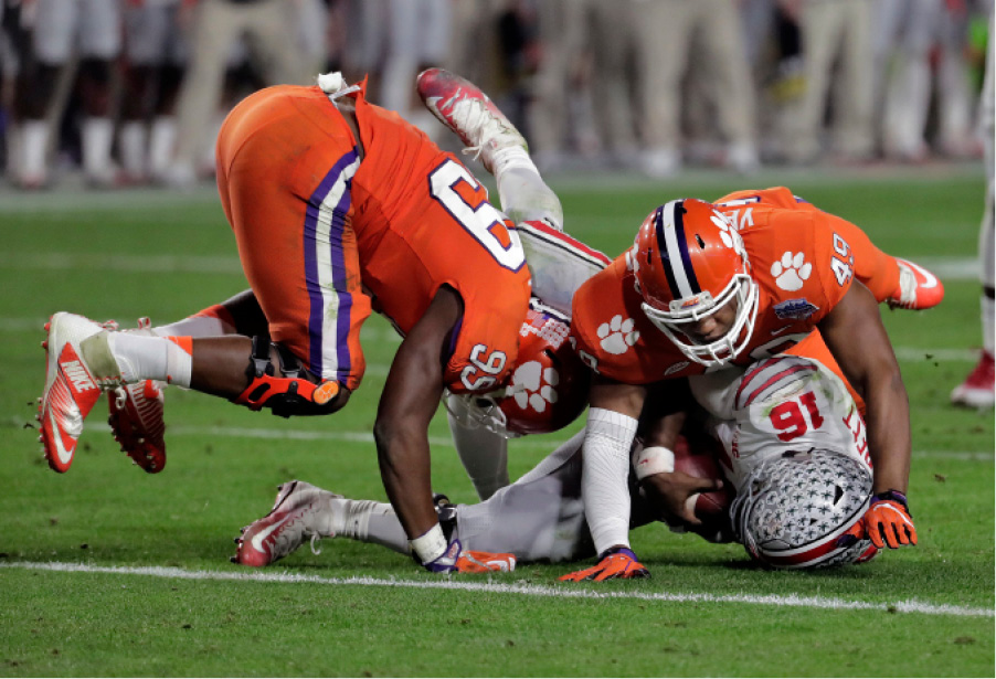 Clemson defensive end Clelin Ferrell (99) sacks Ohio State quarterback J.T. Barrett (16) as defensive end Richard Yeargin (49) falls on Barrett during the second half of the Fiesta Bowl NCAA college football playoff semifinal, Saturday, Dec. 31, 2016, in Glendale, Ariz. (AP Photo/Rick Scuteri)