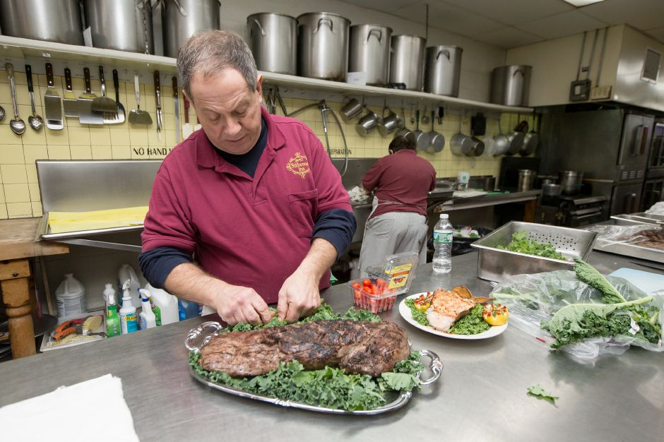 Owner Jim Zandri prepares a beef loin on of the dishes served for the new year celebration Monday at Zandri