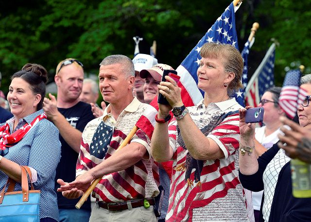 Mary Powell-St. Louis, right, and her husband Tom St. Louis, both of Lyme, Conn., cheer for a speaker during a rally in support of the American Flag on Monday, July 30, 2018 at Higganum Town Green in Haddam, Conn. Protestors and supporters gathered Monday night around a Haddam board of selectmen meeting to address the recent controversy generated by Selectwoman Melissa Schlag