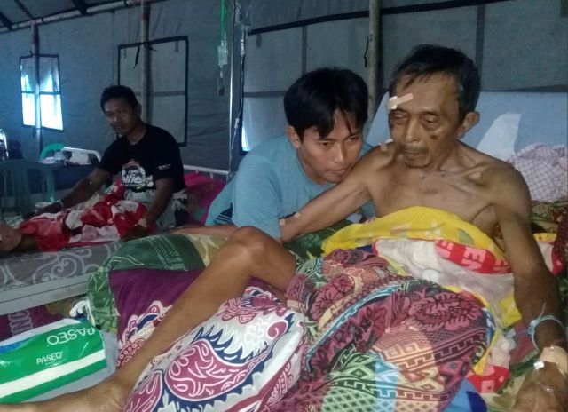 Earthquake-affected patients are treated at a makeshift hospital in Poso, Central Sulawesi, Indonesia, Saturday, Sept. 29, 2018. A powerful earthquake rocked the Indonesian island of Sulawesi on Friday, triggering a 3-meter-tall (10-foot-tall) tsunami that an official said swept away houses in at least two cities. (AP Photo/Yoanes Litha)
