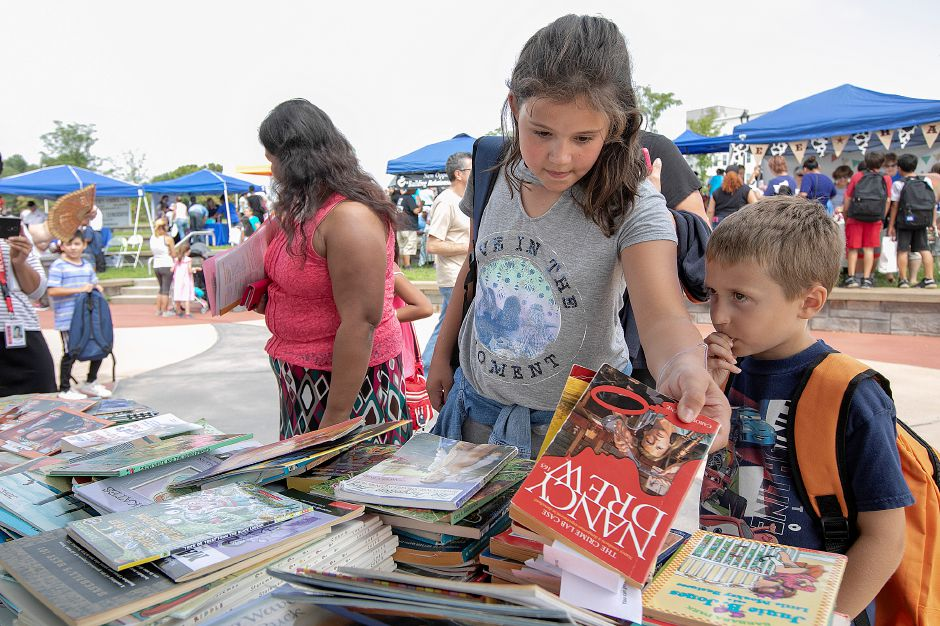 Meira Bismack, 10, of Meriden, and brother, Eli, 7, look over books during the annual Back to School Expo at the Meriden Green, Tuesday, August 21, 2018. Dave Zajac, Record-Journal
