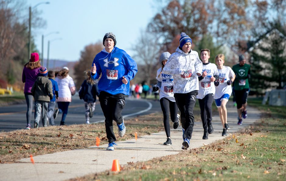 "Runners race along Northwest Drive in Plainville during the ""Thanks for Giving"" race on Oct. 9, 2019. Looping around the Middle School of Plainville, the run raised around $7,000 — over half the money needed to fund the spring sports program at the school. 