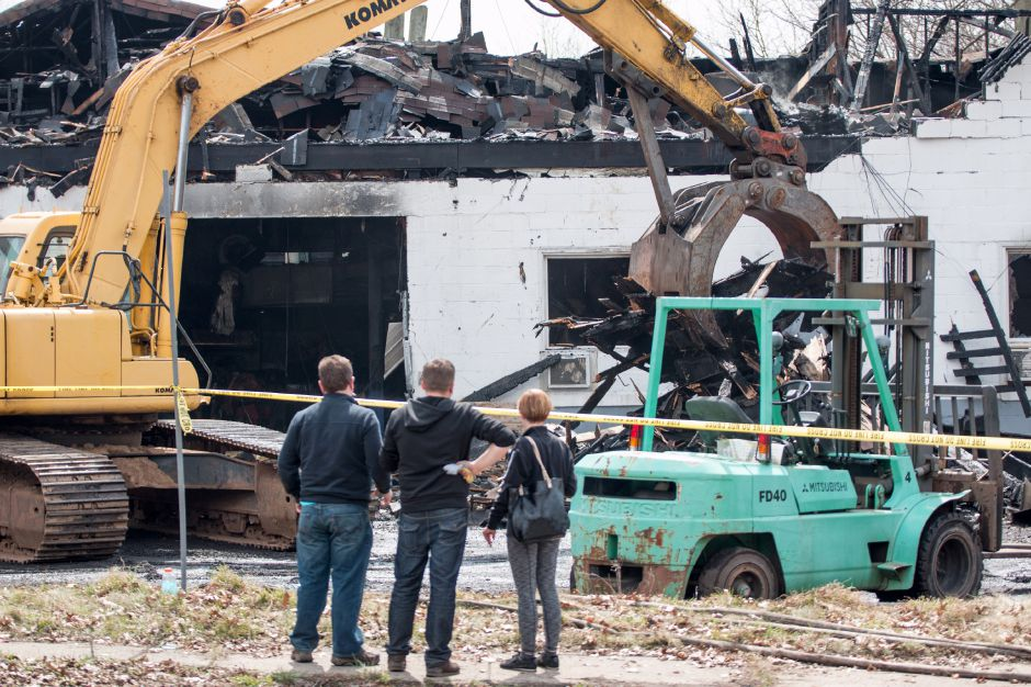 An escavator removes desbris left by a fire at 45 Hall Avenue in Meriden on Friday, April 13, 2018. The building, home to J.C. Recycling Inc., was deemed a total loss. | Devin Leith-Yessian/Record-Journal