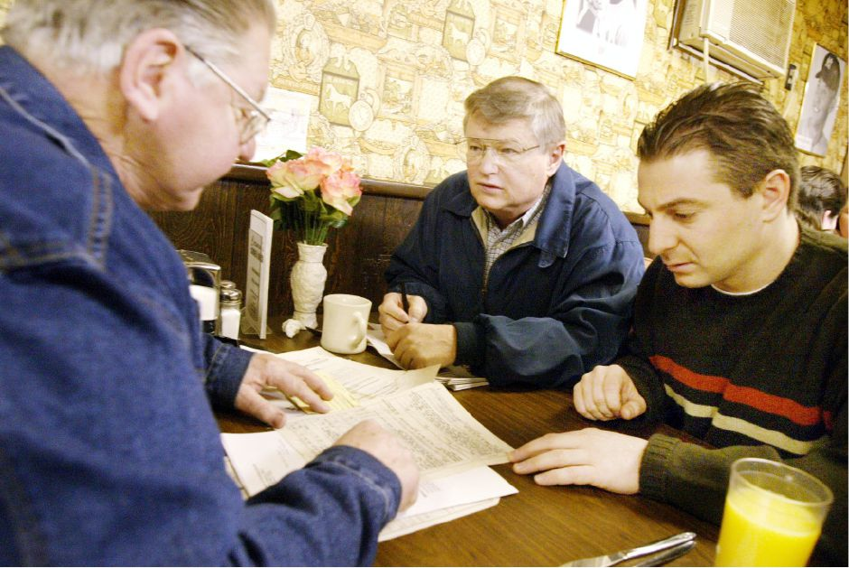 Donald Tempe, left, talks to Meriden City Manager Roger Kemp, center, and Mayor Mark Benigni, right, about a veterans concern Dec. 14, 2002 at Carmen