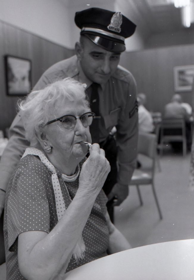 Meriden Police officers give whistles to the elderly, August 1975.