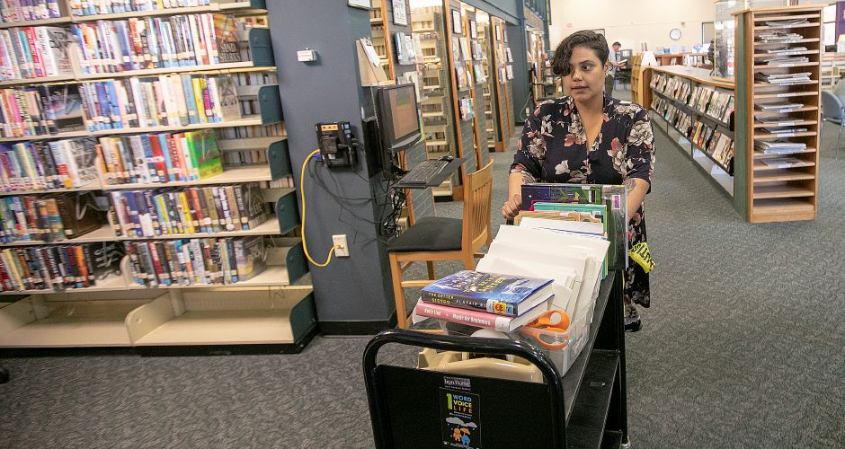Jasmine Cedeno, library assistant, transfers a cart of books at the Southington Public Library, Mon., May 6, 2019. The library will hold an information session on the library