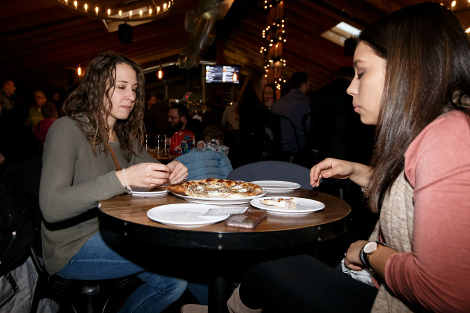 Melanie Romaniw of Southington left and Katherine Hansen of Milford enjoys a pizza Saturday at Sauced at Kinsmen in the Kinsmen Brewery in Southington February 10, 2018 | Justin Weekes / Special to the Record-Journal