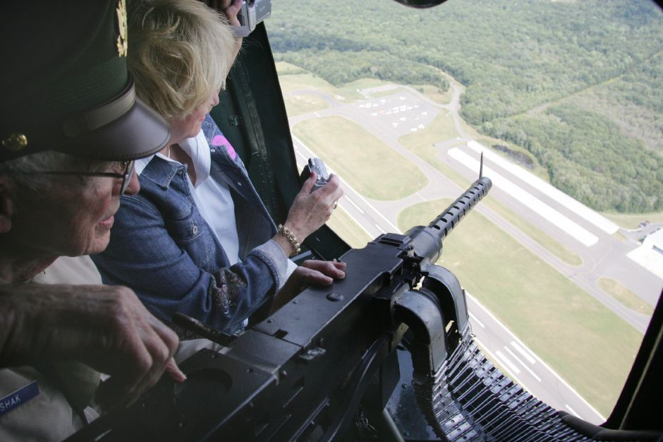 Walter Hushak and Gail Doerfler look through the opening for the waist gunner posistion as the B-24J flies over Oxford Airport to set up for it