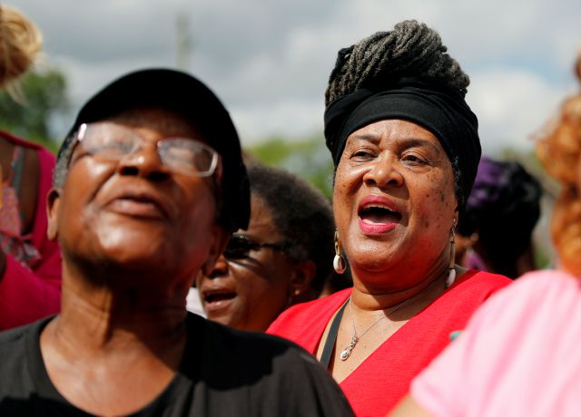 Women sing outside New Bethel Baptist Church where a viewing for Aretha Franklin is being held ,Thursday, Aug. 30, 2018, in Detroit. Franklin died Aug. 16, 2018 of pancreatic cancer at the age of 76. (AP Photo/Jeff Roberson)
