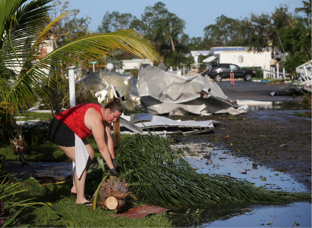 Karyn Chapman cleans up debris in front of her destroyed home in the aftermath of Hurricane Irma in the Naples Estates mobile home park, in Naples, Fla., Tuesday, Sept. 12, 2017. (AP Photo/Gerald Herbert)