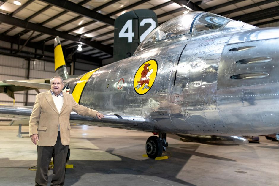 Robert Rawlings, of Berlin, stands in front of an Air Force F-86, the jet fighter model he flew in the Korean War. Rawlings was presented with replacement service medals at the New England Air Museum in East Granby on Nov. 27, 2018. | Devin Leith-Yessian/Berlin Citizen