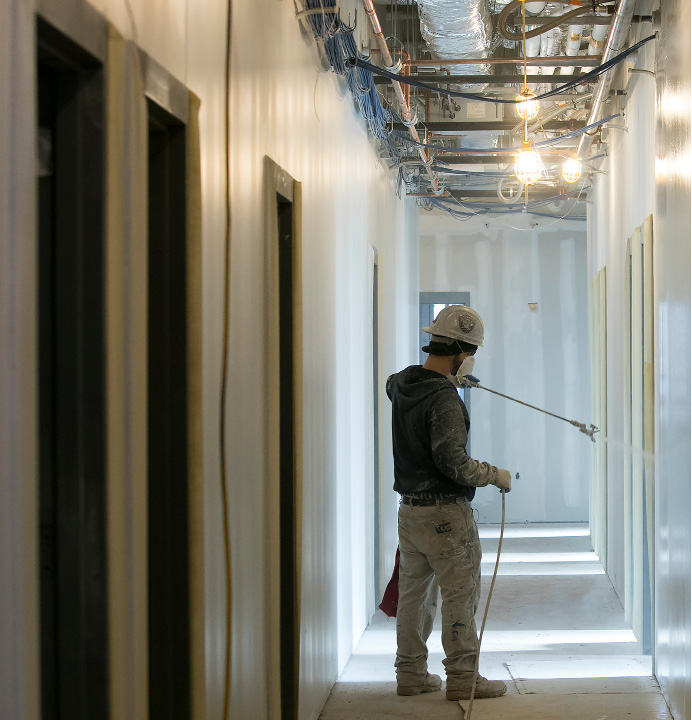 A worker paints a hallway as construction continues at Platt High School in Meriden, Friday, February 24, 2017.  | Dave Zajac, Record-Journal