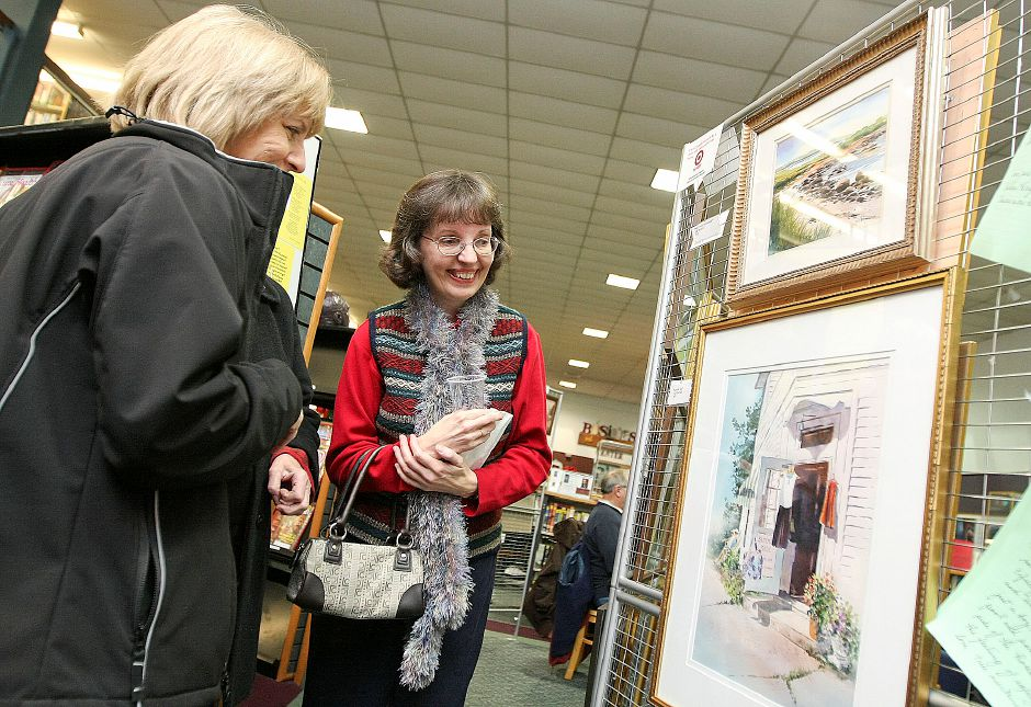 "Southington Public Library ranks eigth on TripAdvisor.com's list of things to do in Southington. In this file photo, Gail Bannock (left) of Southington, shows Cathy Michanczyk, of Plantsville, her two watercolor paintings at ""A Celebrate the Arts"" exhibit at the Southington Public Library in Southington on December 8, 2010. (Matt Andrew/ Record-Journal)"
